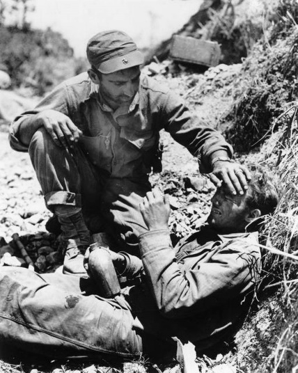 A U.S. Marine comforts a comrade, who witnessed the death of his buddy, hillside in the Vincinity of Shuri, in May 1945, during the invasion of Okinawa, Japan. (AP Photo)